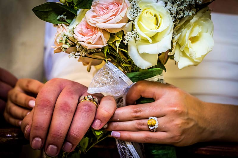 Person wearing gold ring holding white rose bouquet