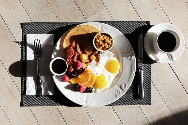 Plate of egg, berries, and pancake with a cup of coffee