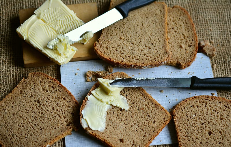 Sliced bread on brown wooden chopping board