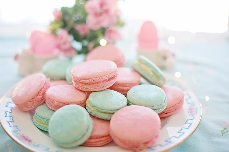 Pink and white heart shaped cookies on white and blue ceramic plate