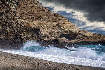 Brown rocky mountain beside sea waves under cloudy sky during daytime