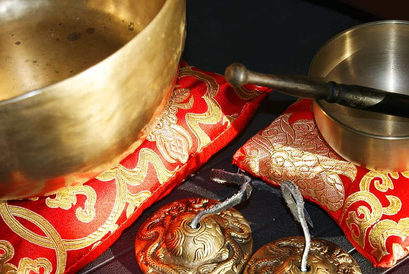 Black and silver mortar and pestle on red and gold floral pillow