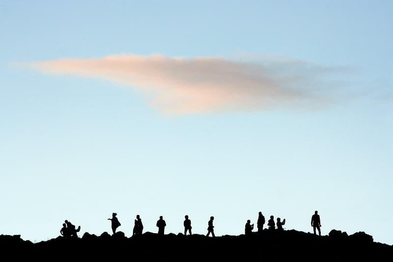 Silhouette of people on top of hill