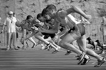 Grayscale photo of athletes running in field