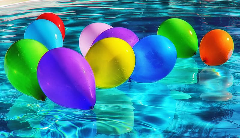 Assorted-color inflated balloons floating in pool of water