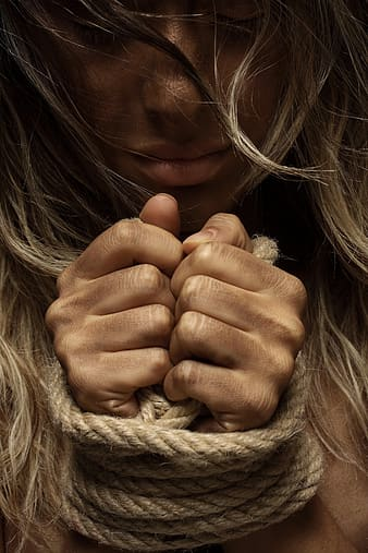 Woman's hands tied with a rope
