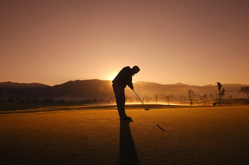 Silhouette of man holding golf club during sunset