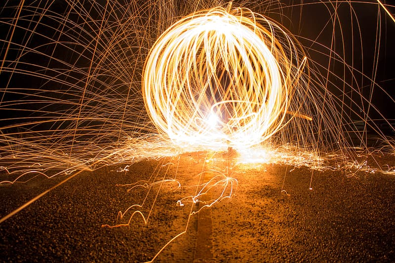 Steel wool photography of person standing on brown sand