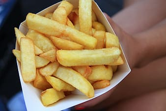 Person holding box of French fries