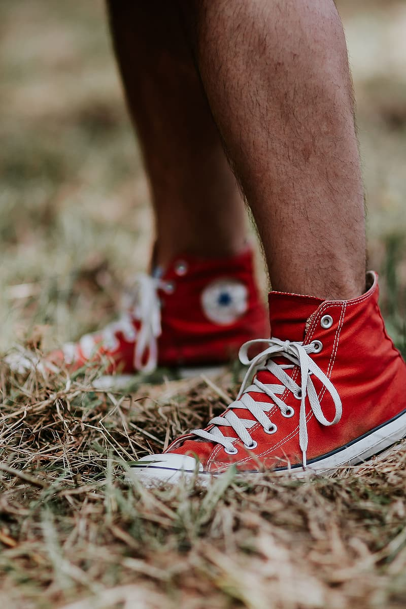 Person wearing red converse all star high top sneakers