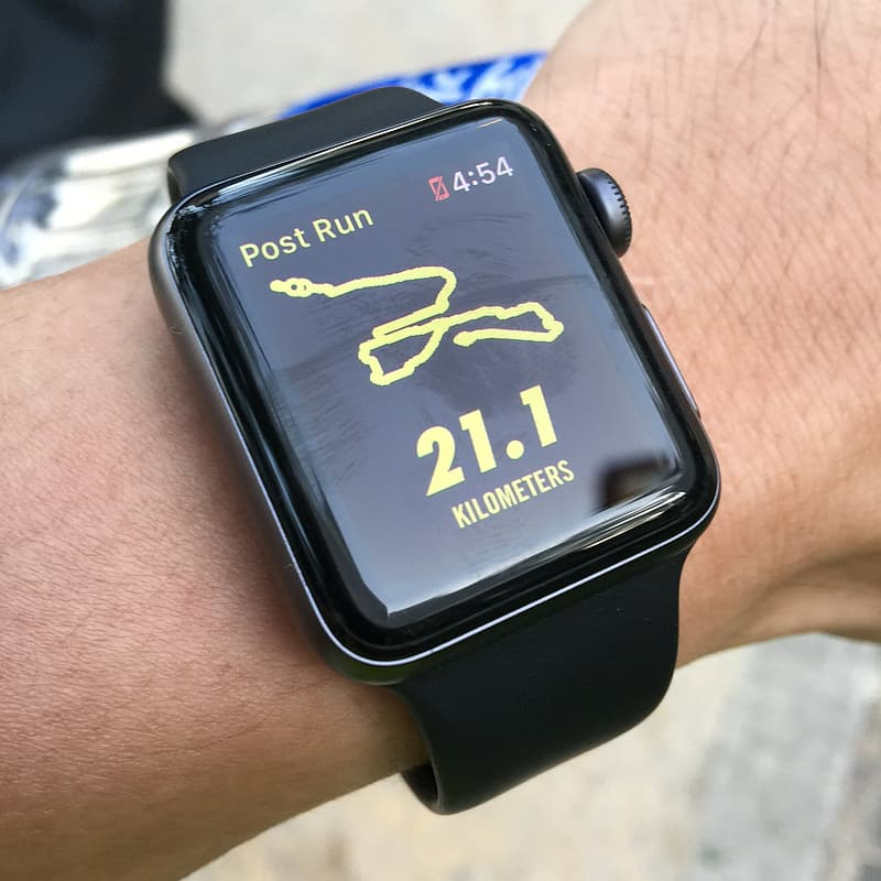 Person wearing space gray Apple Watch with black Sport Band displaying 21.1 kilometers