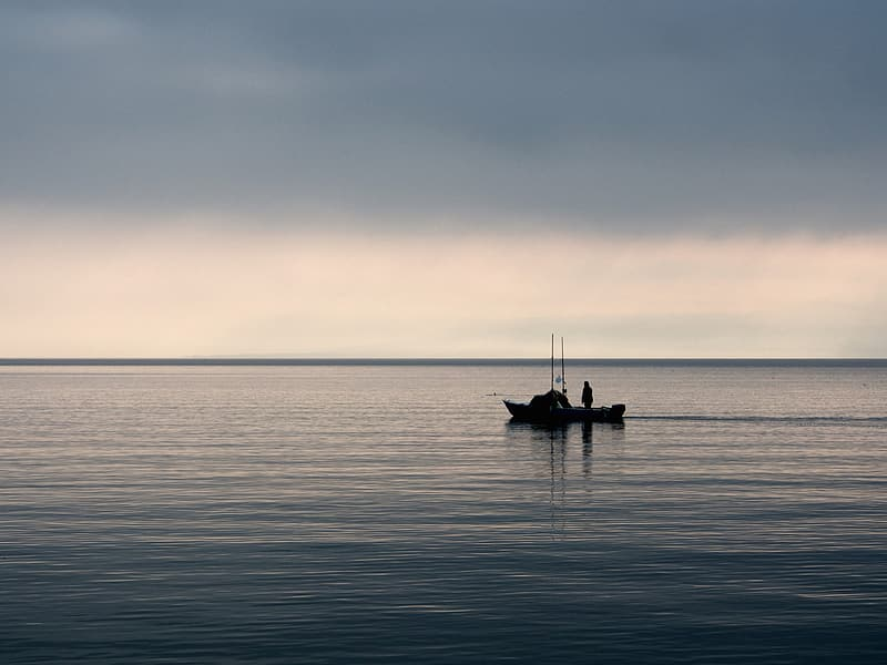 Silhouette of 2 people riding boat on sea during daytime