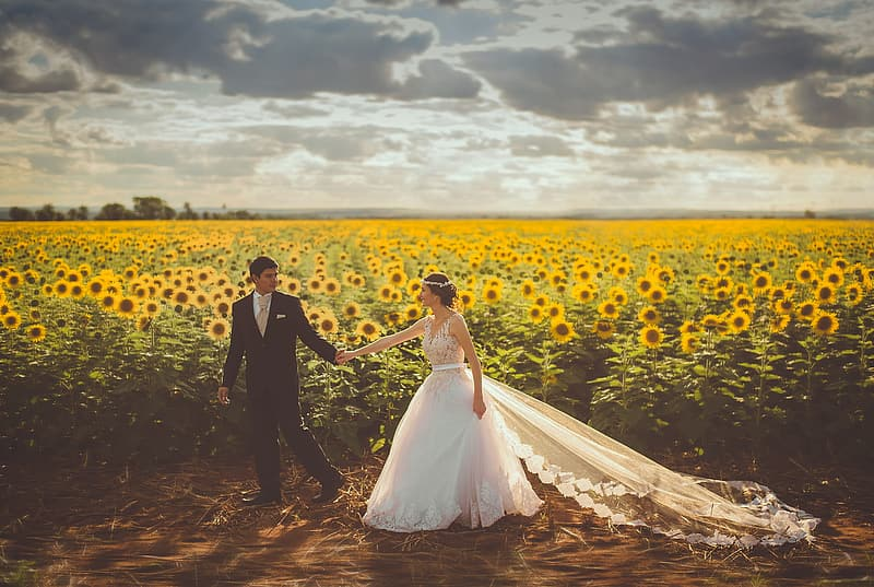 Man and woman in wedding dress walking on dirt road between yellow flower fields during daytime