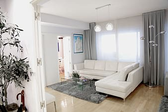 White leather sectional sofa in front of window with sheer white and gray curtain