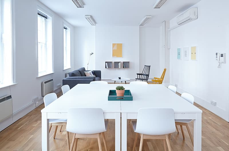 Two rectangular white wooden tables with chairs