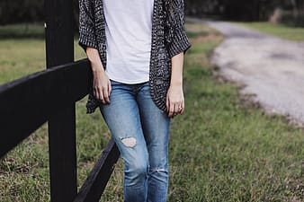 Person wearing black cardigan and distressed blue denim jeans