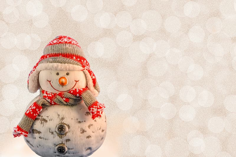 White and red snowman wearing knit hat and scarf figurine