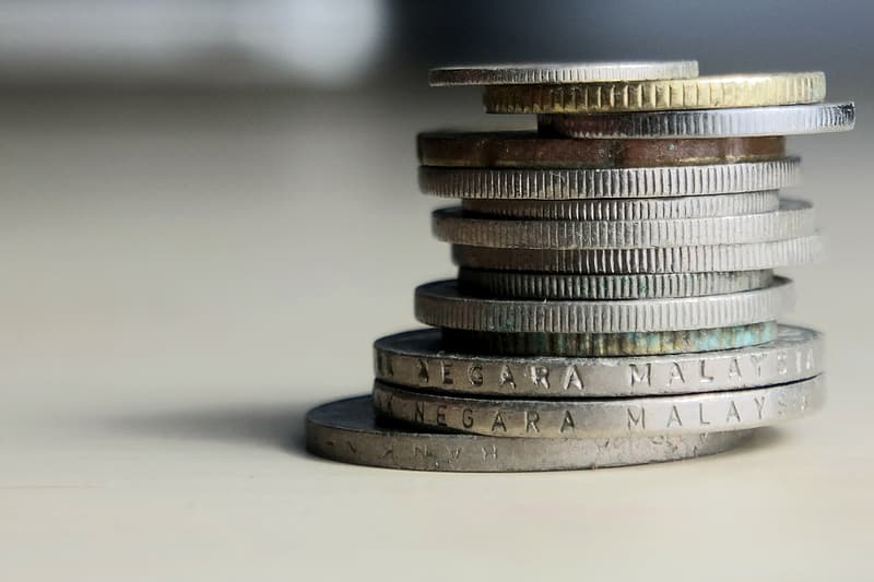 Selective focus photography of stack of coins on white table