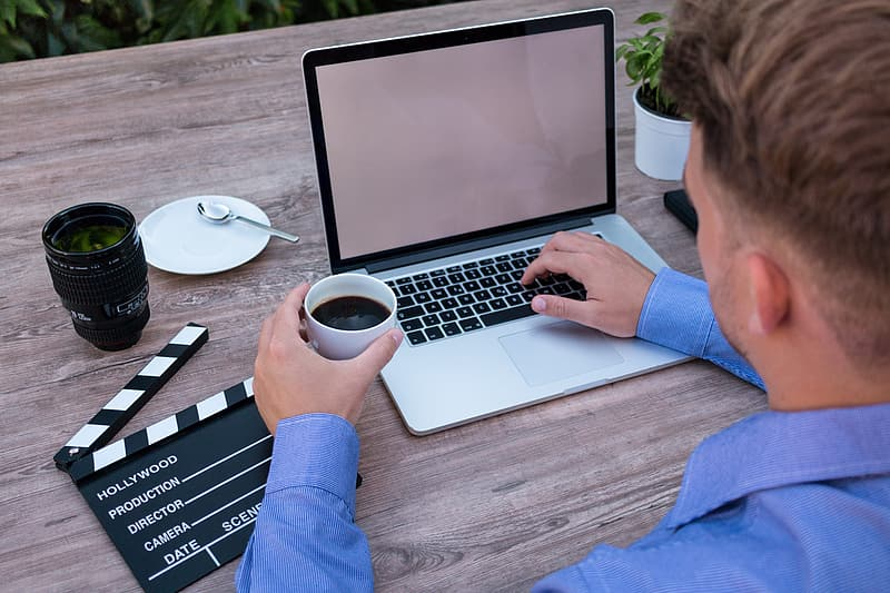 Man in blue dress shirt in-front of laptop computer