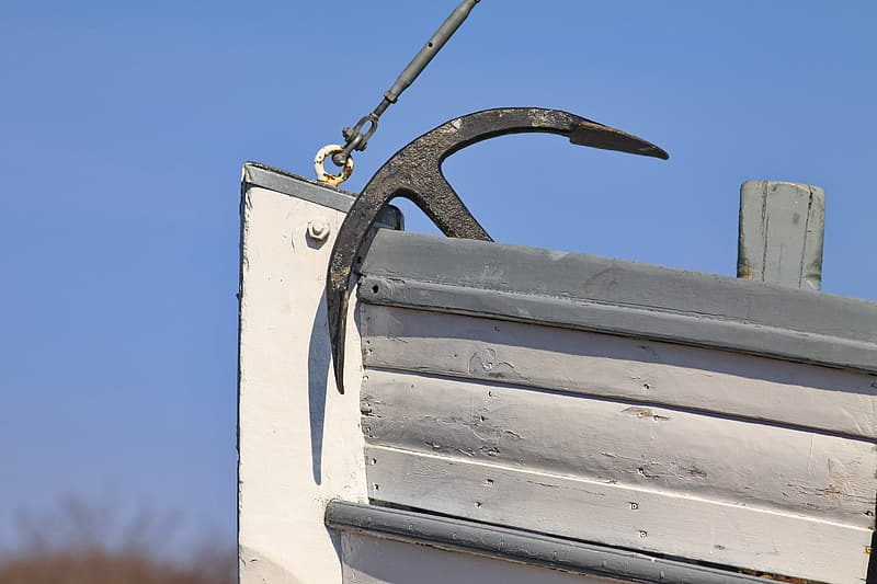 Black boat anchor on white boat photography during daytime
