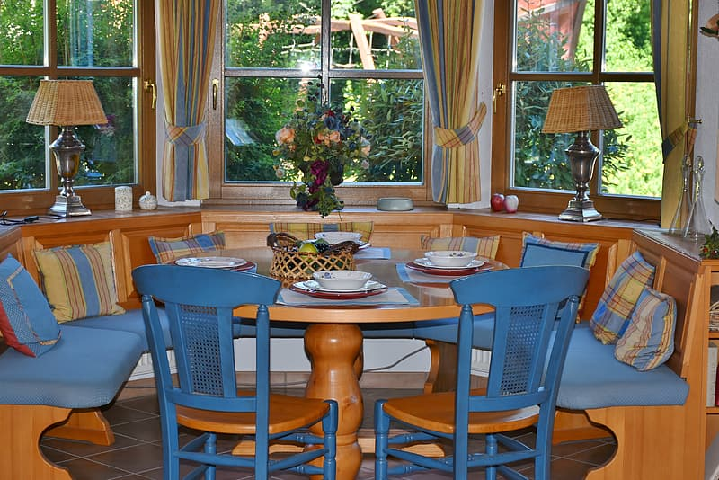 Brown wooden dining table with chairs near window