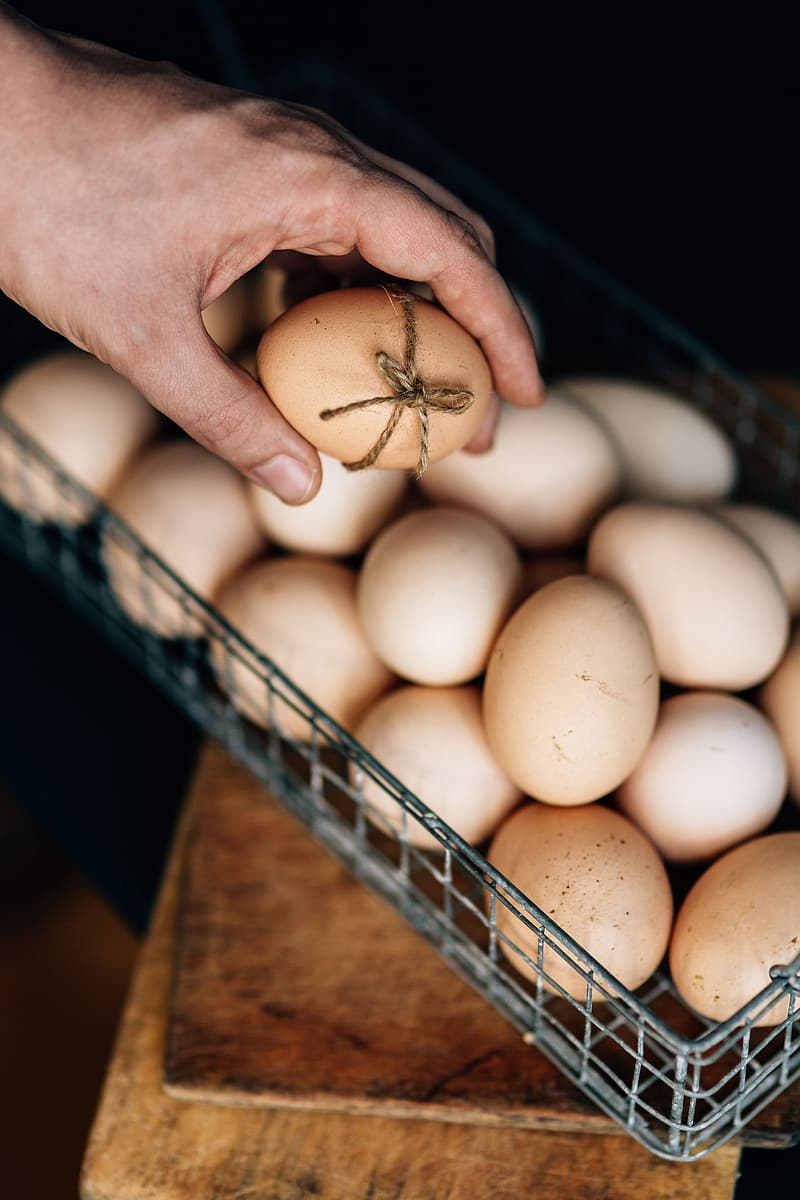 Person holding brown eggs in tray