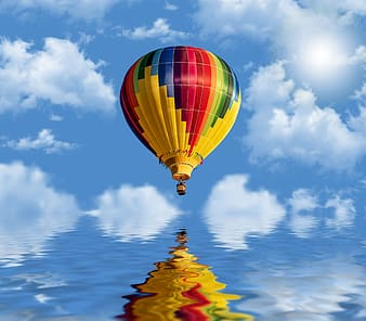 Yellow green and red hot air balloon under blue sky and white clouds during daytime