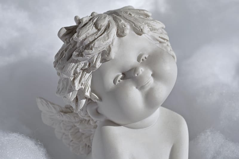Shallow focus photography of angel figurine