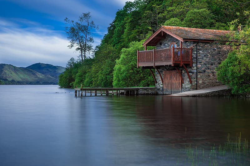 Brown wooden house near body of water during daytime