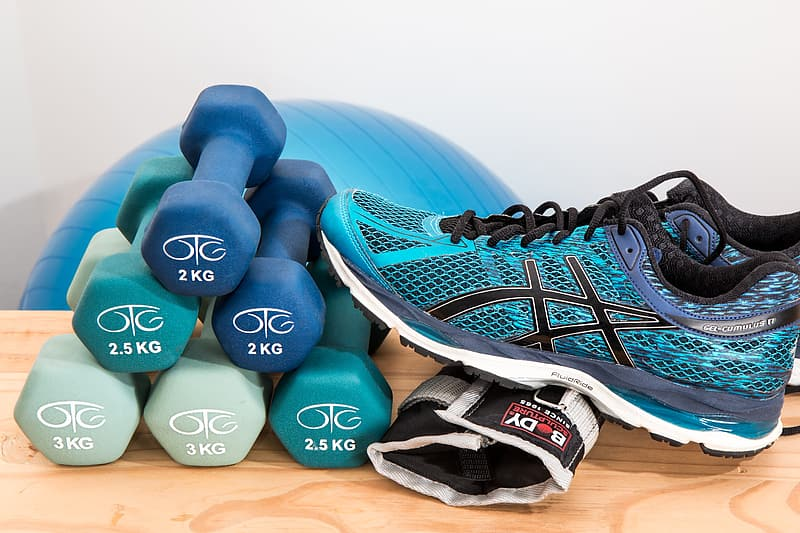 Six 2 kg fixed weight dumbbells and Asics running shoe on brown table