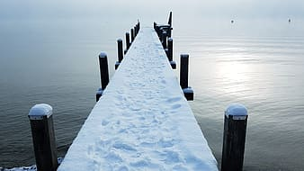 Snow covered wooden dock during daytime