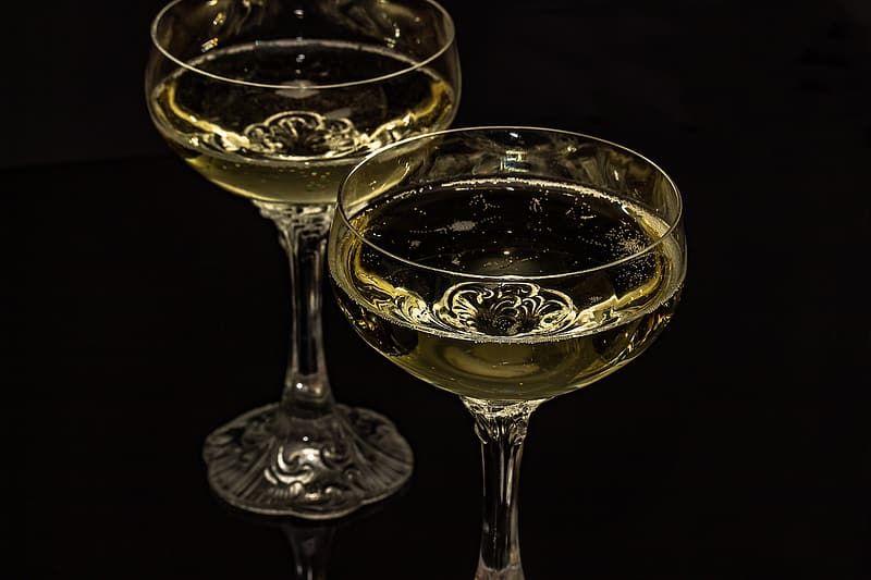 Two clear cocktail glasses on black surface close-up photo