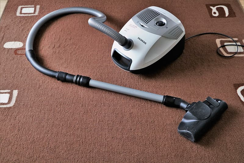 Gray and white wet dry vacuum on brown area rug