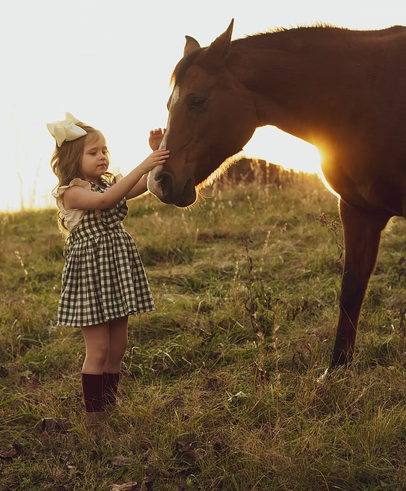 Girl in black and white checkered dress standing beside brown horse during daytime