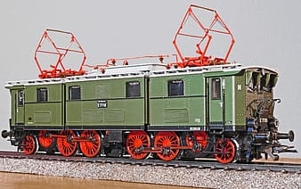Green and red train on rail tracks