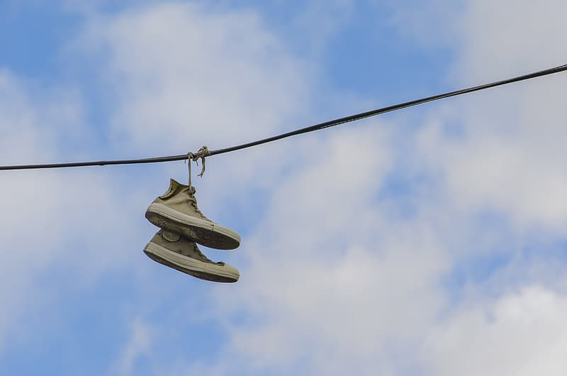 White and gray nike sneakers hanging on black wire during daytime