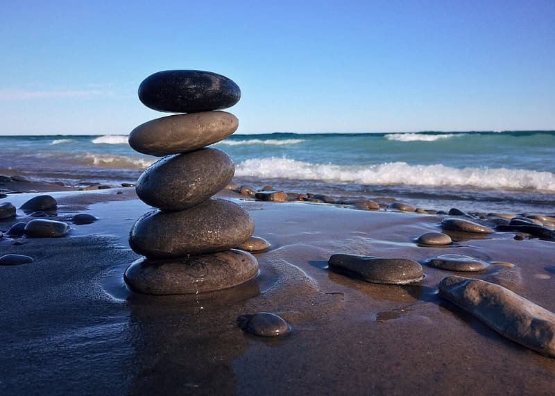 Gray stacked stone beside body of water
