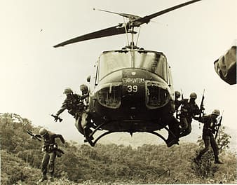Grayscale photo of soldiers jumping off helicopter