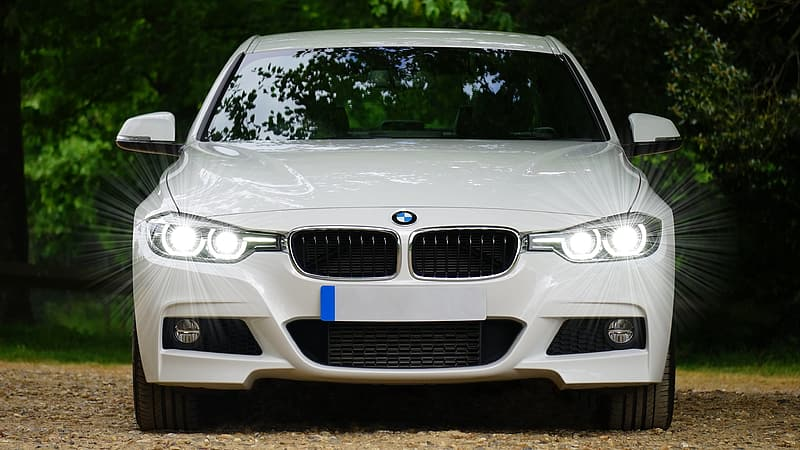 White BMW 5 series with headlights turned on at daytime