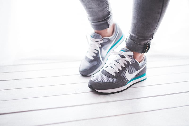 Person wearing gray-and-white Nike running shoes