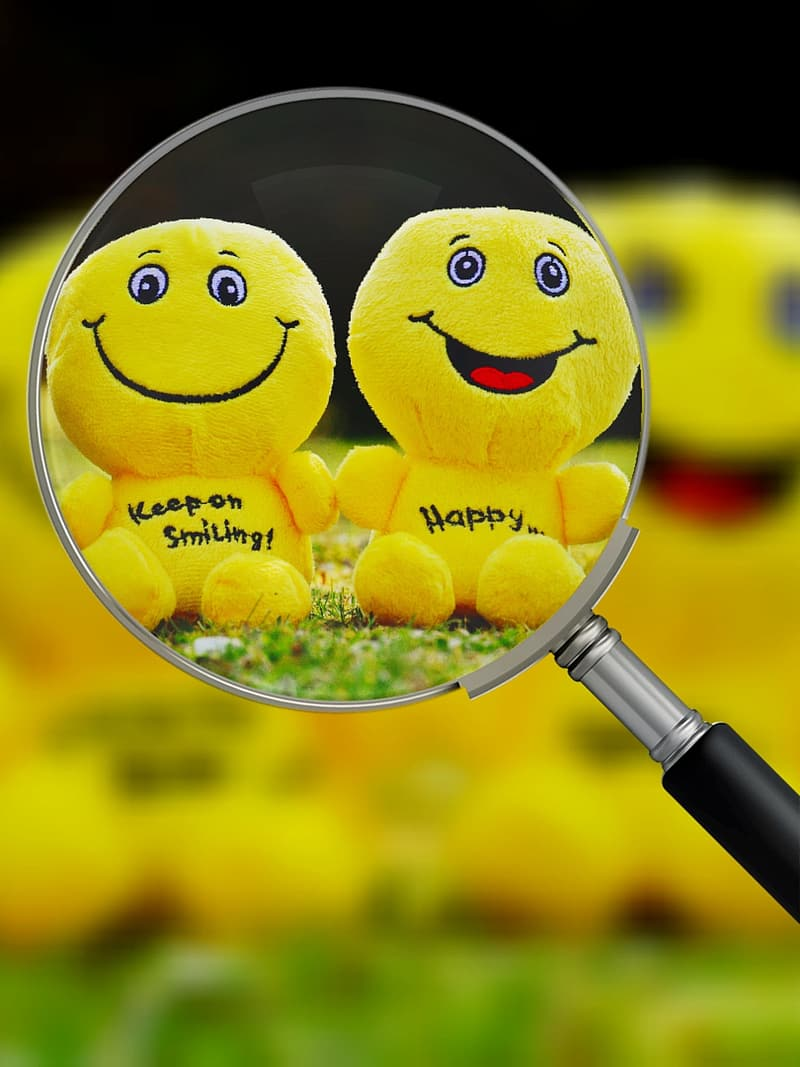 Two yellow emoji plush toys in magnifying glass