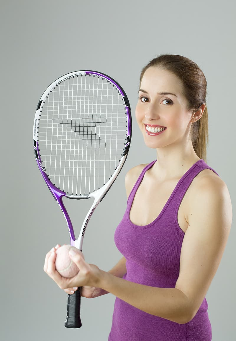 Woman in purple tank top holding tennis racket and ball