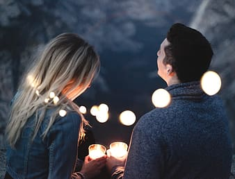 Man and woman holds pillar candles
