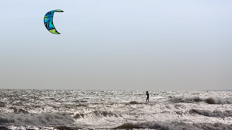 Person in black jacket holding green and blue kite surfing on beach during daytime