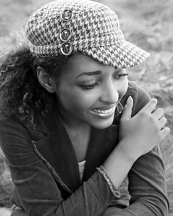 Smiling woman wearing denim notched lapel jacket and houndstooth cap