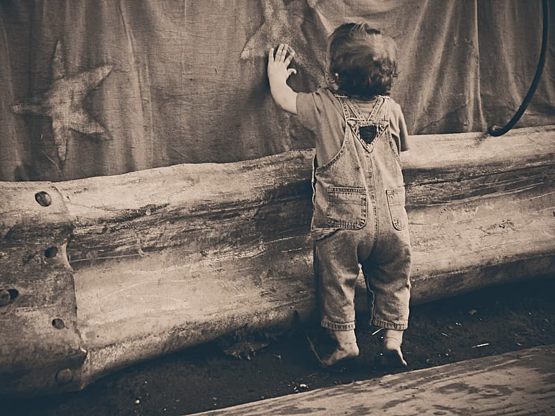 Grayscale photo of child in button up shirt and pants standing beside tree trunk