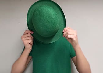 Person wearing green shirt covering face with green hat