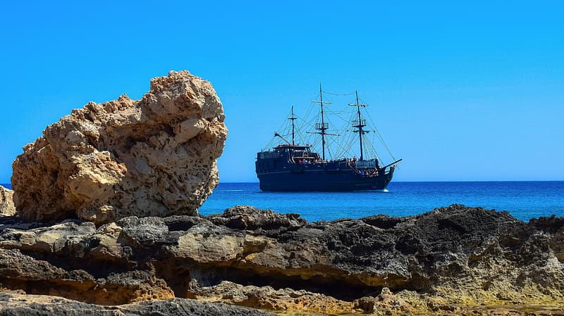 Black galleon ship on a calm body of water