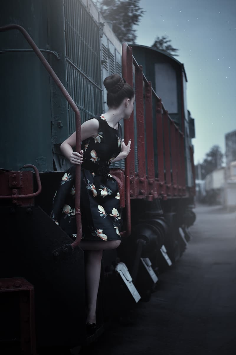 Woman in black and brown floral sleeveless mini dress on red and green locomotive train