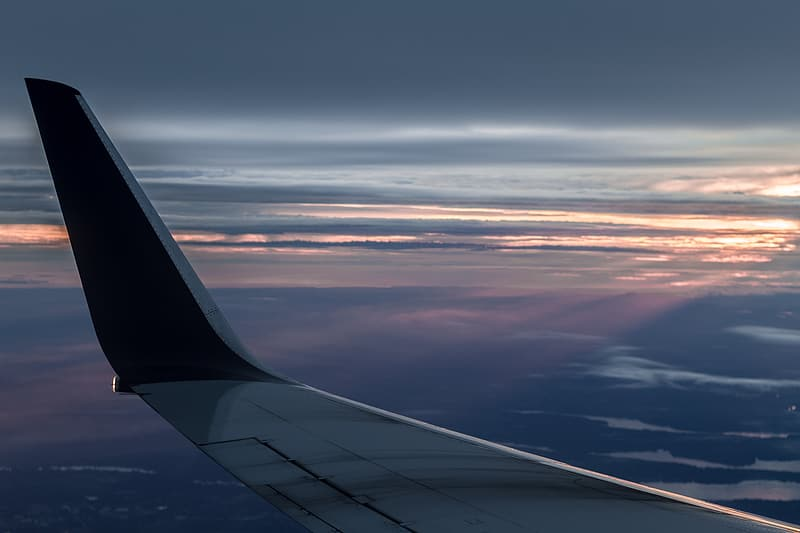 Black and gray airplane wing with view of cloudy horizon